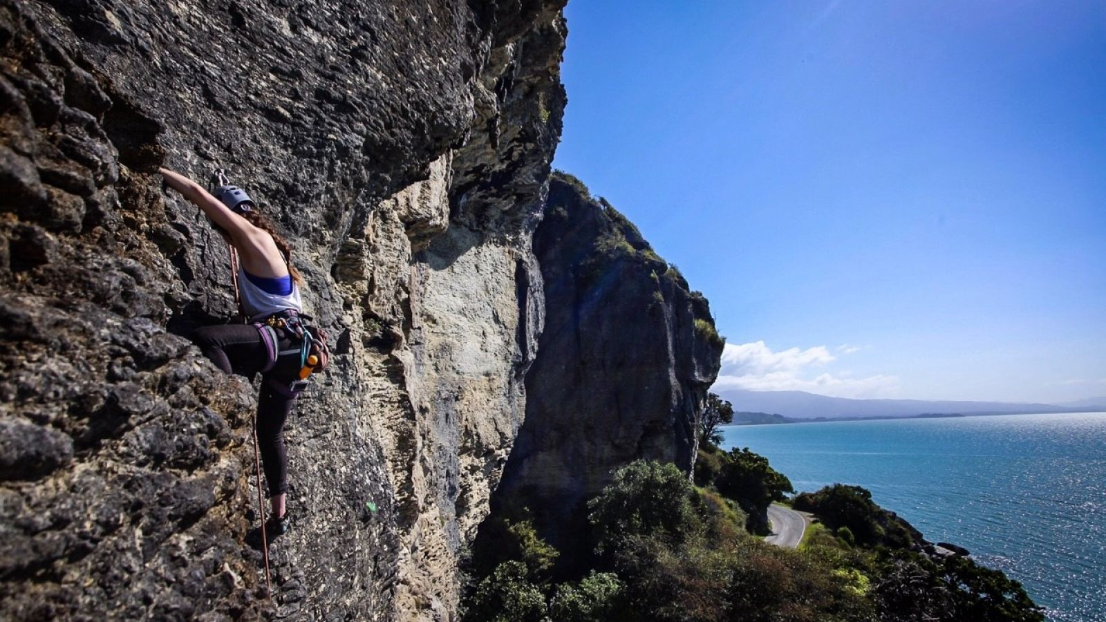 Female Climbing Wall Ocean Backdrop